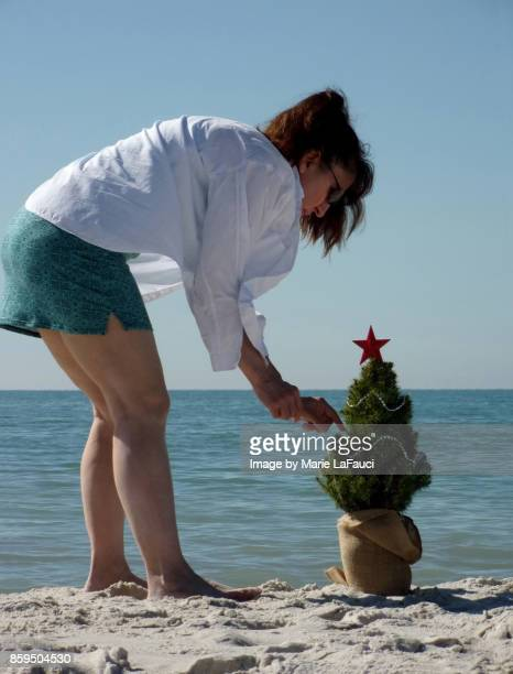 Woman decorating a tiny Christmas tree at the beach