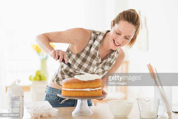 Woman decorating cake in kitchen
