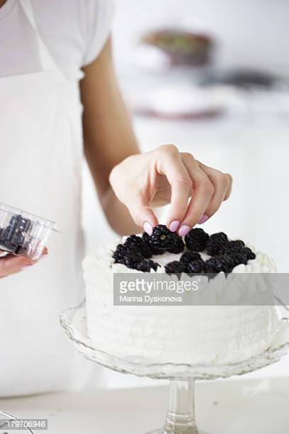 Woman decorating cake with fresh blackberries