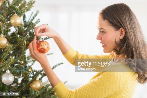 Woman decorating christmas tree : Stock Photo