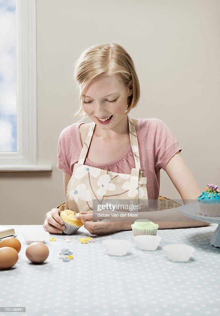 woman decorating cupcake.
