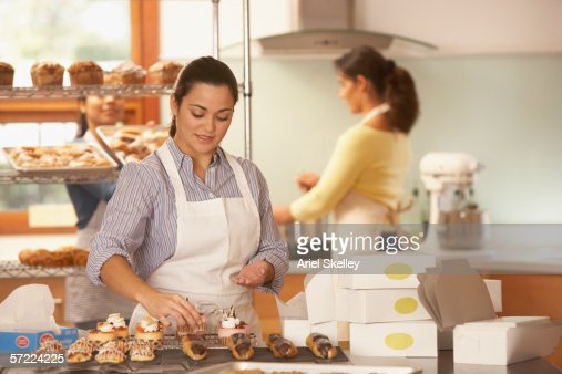 Woman Decorating Cupcakes woman decorating cupcakes in bakery stock photo | getty images