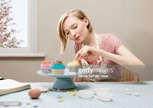 woman decorating cupcakes stock photo getty images