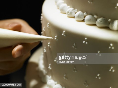 Woman decorating layered cake with icing bag, close-up of cake : Stock Photo