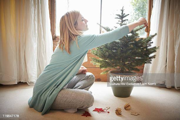 Woman decorating small Christmas tree