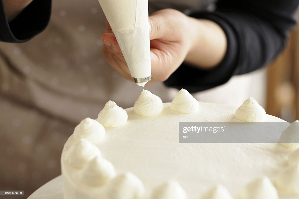 Woman decorating whipped cream on cake : Stock Photo