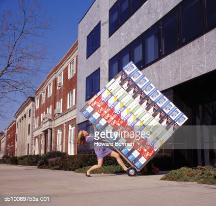 Woman delivering heavy boxes, side view : Stock Photo