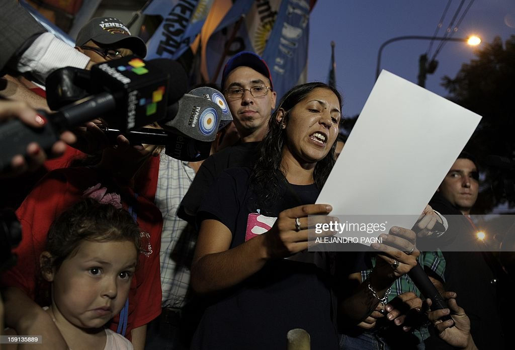 A woman delivers a speech during a rally in support of Venezuelan President Hugo Chavez´s recovery in front of the Venezuelan embassy in Buenos Aires on January 8, 2013. The President of the National Assembly Diosdado Cabello announced today that due to health reasons, Chavez will not be able to take the oath to be sworn in for a fourth term in office next January 10. A constitutional fight intensified with the government planning a massive show of support in the streets on the day he is supposed to be sworn in. Chavez, who underwent his fourth round of cancer surgery in Havana nearly a month ago, is suffering from a severe pulmonary infection that has resulted in a respiratory insufficiency. The sign reads 'Long live Commander Chavez. Long live Nestor (Kirchner), Strength Cristina (Fernandez). We are overcoming'. AFP PHOTO / ALEJANDRO PAGNI