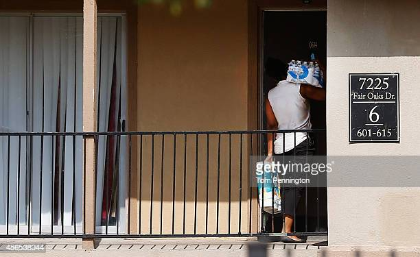 A woman delivers bottled water and toilet paper to residents in a unit at the Ivy Apartments where the confirmed Ebola virus patient was staying on...
