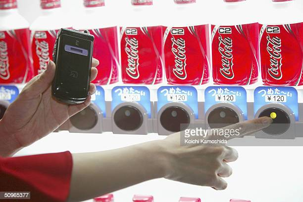 A woman demonstrates how to buy a soft drink from a vending machine with NTT DoCoMo's mobile phone handset equipped with Sony's IC card technology...