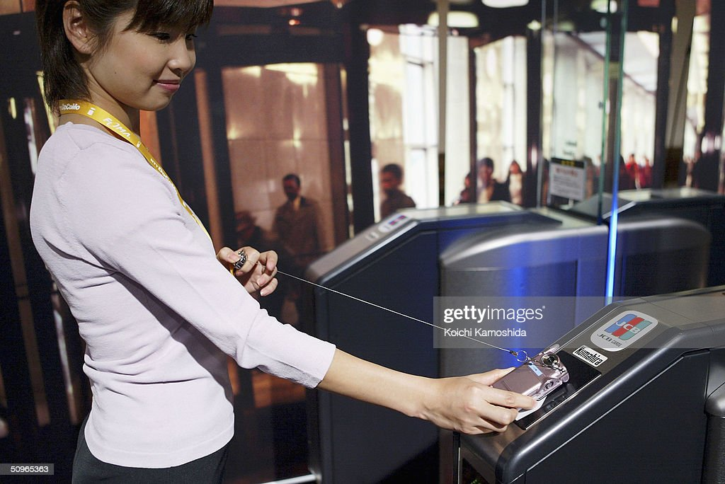 A woman demonstrates how to go through the railway ticket barrier paying with NTT DoCoMo's mobile phone handset equipped with Sony's IC card...