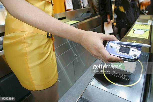 A woman demonstrates how to go through the ticket barrier of East Japan Railway paying with your phone rather than a ticket during a business show on...