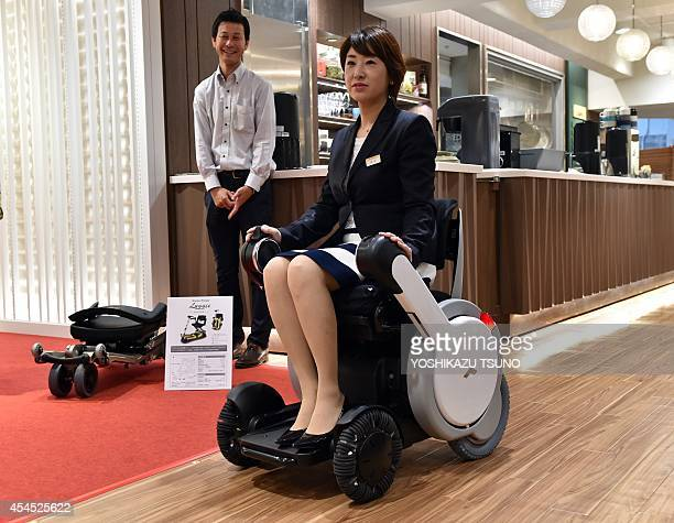 A woman demonstrates the new electric wheelchair 'Whill model A' produced by Japan's personal mobility venture Whill at the Mitsukoshi department...