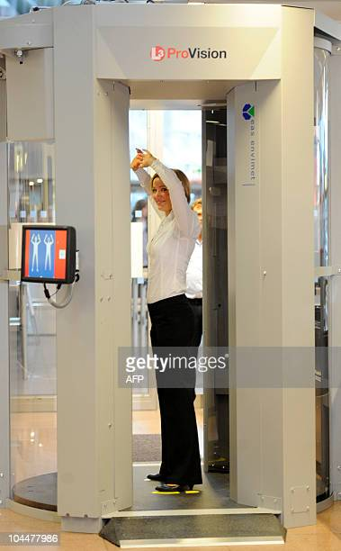A woman demonstrates the use of a full body scanner at the airport Fuhlsbuettel in Hamburg northern Germany on September 27 2010 The scanners are...