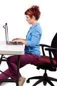 young woman demonstrating proper office desk posture by sitting near the edge of the seat