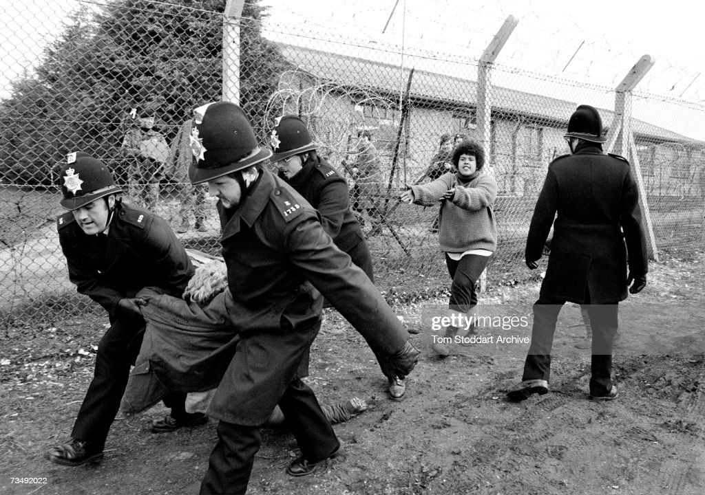 A woman demonstrator is arrested as a friend pleads for her release during protests by anti-nuclear campaigners opposed to the deployment of the nuclear missiles at Greenham Common air base in Berkshire, December 1983.