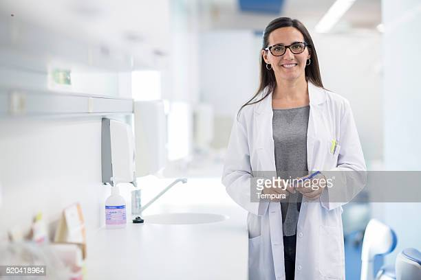 Mujer Retrato de dentista observando a la cámara.