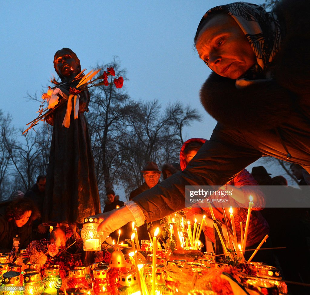 A woman deposits a candle in memory of the victims of the Holodomor famine during a ceremony at the Holodomor memorial in Kiev on November 24, 2012. Ukraine marked 80 years since the Stalin-era Holodomor famine, one of the darkest pages in its entire history that left millions dead and which is regarded by many as a genocide. The 1932-33 famine took place as harvests dwindled and Josef Stalin's Soviet police enforced the brutal policy of collectivising agriculture by requisitioning grain and other foodstuffs. AFP PHOTO/ SERGEI SUPINSKY