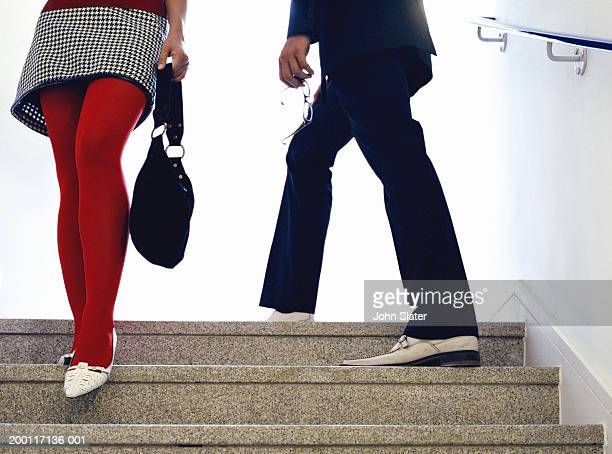 Woman descending stairs passing man ascending, low section