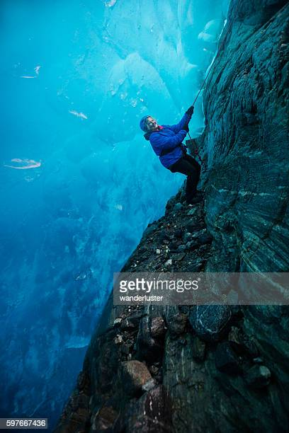 Woman descends into blue ice cave by rope