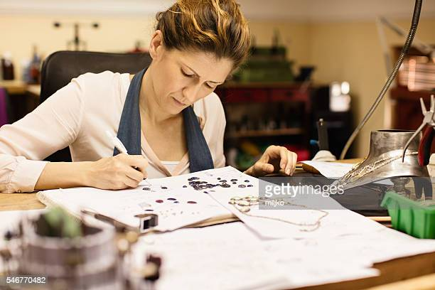 Woman designer makes and design jewelry in workshop