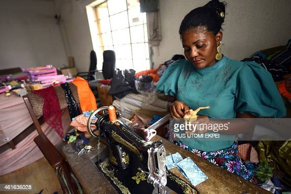 A woman designs doll clothes to give it an African look at Taofick Okoya's Fico Solutions workshop in Lagos on December 17 2014 Creator of the...