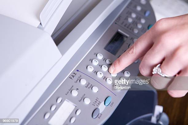 Woman dialing a number to send a fax