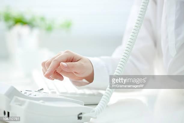 Woman dialing landline phone