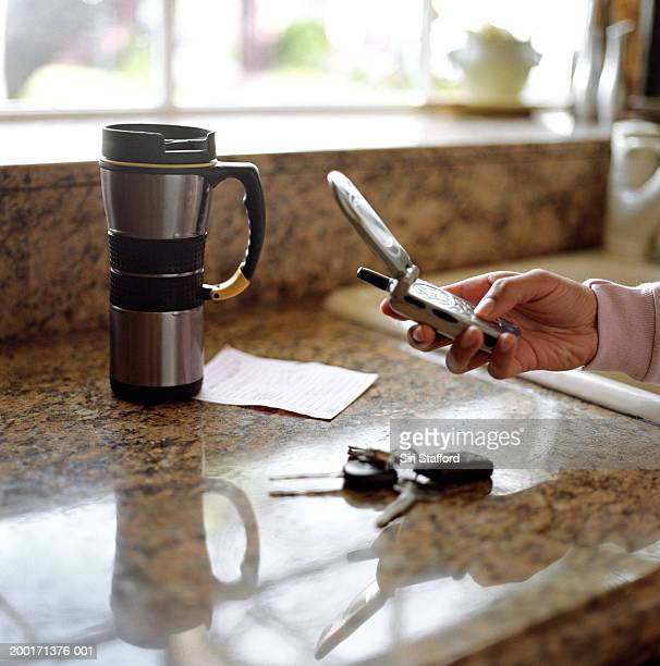Woman dialing mobile phone over kitchen counter
