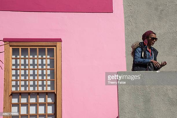 A woman dials a number on a mobile phone in the BoKaap township formely known as the Malay Quarter This township buit on the slopes of Signal Hill is...