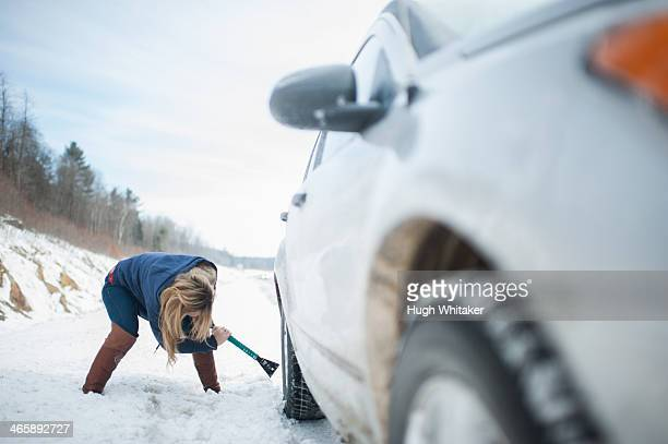 Woman digging car out from snow