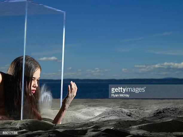 woman digging out of glass cube in sand