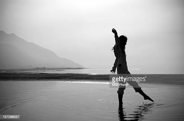 A woman dipping her toe in to the sea