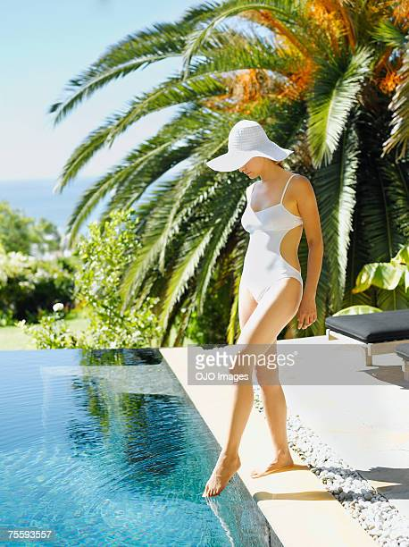 Woman dipping her toes in a pool
