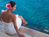 Woman dipping her toes in a pool with a white towel around her