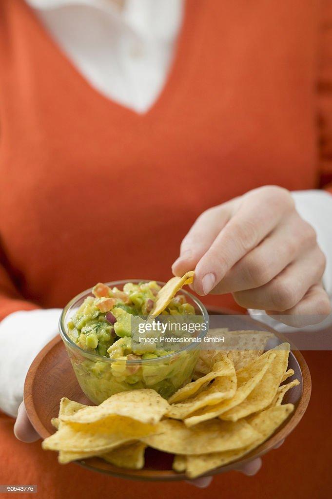 Woman dipping nacho in guacamole, close up : Stock Photo