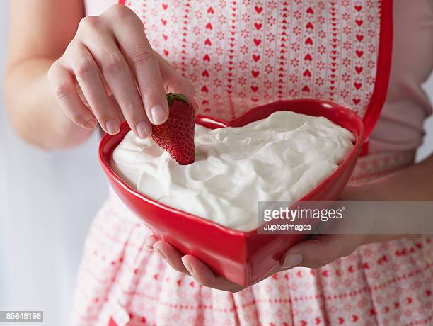 Woman dipping strawberry into bowl of whipped cream