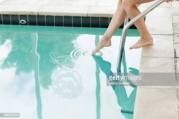 Woman dipping toe in swimming pool