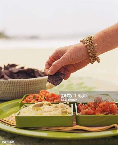 Woman dipping tortilla chip into hummus