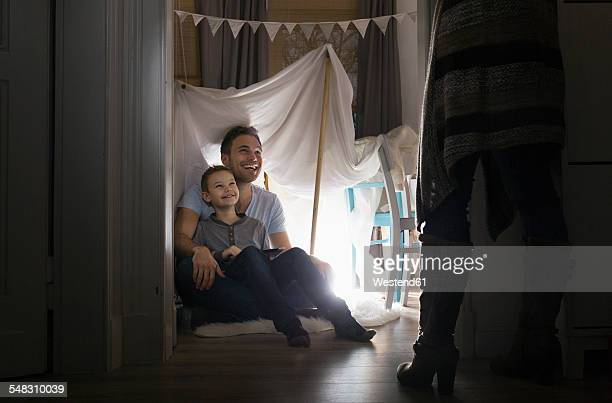 Woman discovering husband and son in self-made tent at home