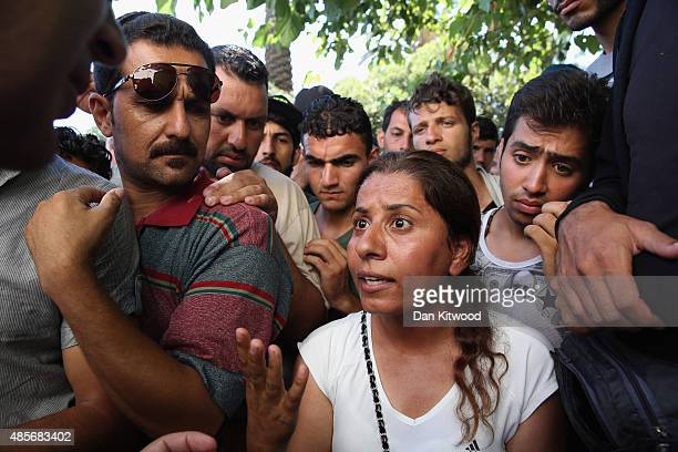 A woman discusses the slow process in acquiring her transit papers with a member of the UNHCR on August 29 2015 in Kos Greece Migrants from many...