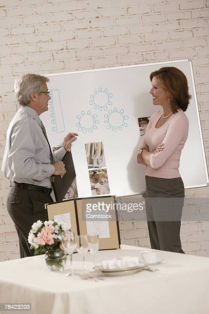Woman discussing seating chart with  wedding planner