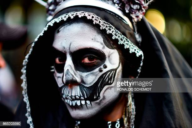 TOPSHOT A woman disguised as 'Catrina' takes part in the 'Catrinas Parade' along Reforma Avenue in Mexico City on October 22 2017 Mexicans get ready...