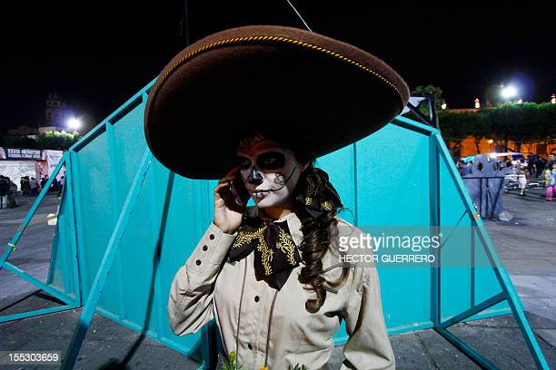 A woman disguised as 'Catrina' talks on a phone during the celebration of the day of dead in Guadalajara Mexico on November 02 2012 La catrina is the...