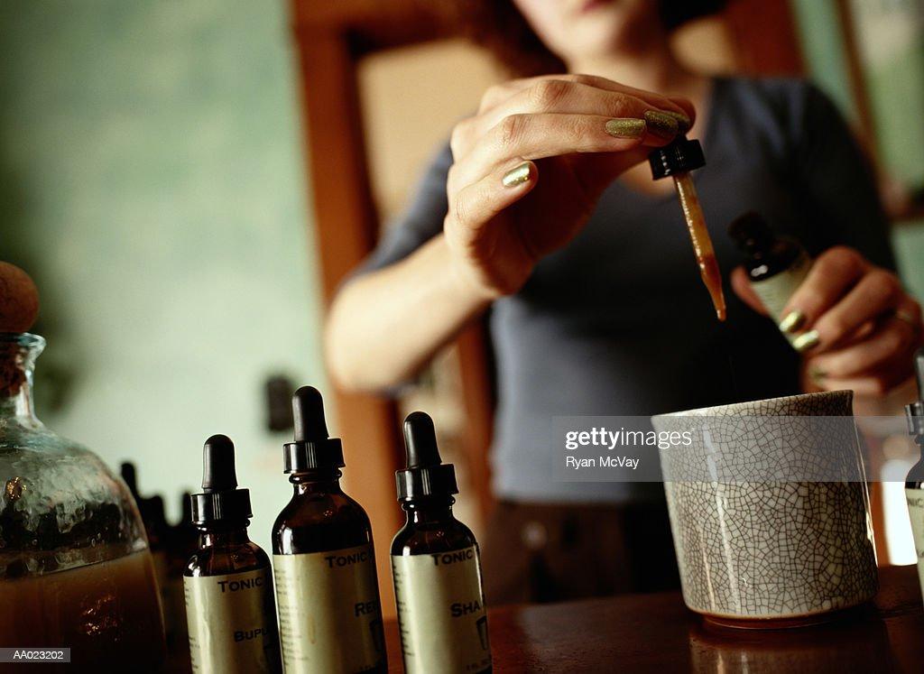 Woman Dispensing an Eyedropper of Herbal Tonic