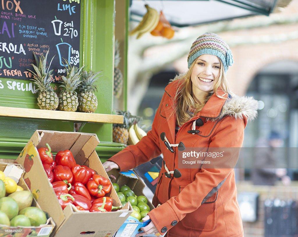 Woman displaying fruit outside juice bar.