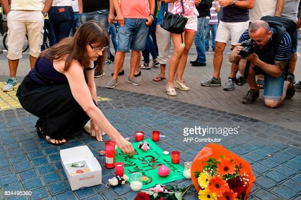 A woman displays a candle next to first flowers and a message to the victims on August 18 2017 on the spot where yesterday a van ploughed into the...