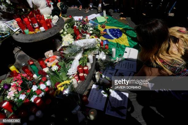 TOPSHOT A woman displays a candle next to flowers messages stuffed toys and many differents objects for the victims on August 18 2017 on the spot...