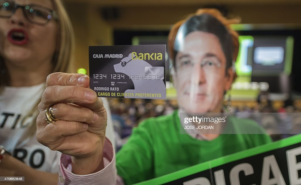 A woman displays a fake Bankia credit card of Rodrigo Rato as she protests against fraud during the Bankia Shareholders Extraordinary General meeting...