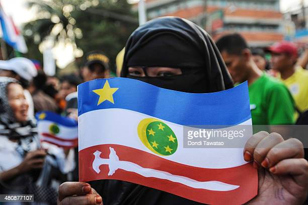 A woman displays a flag of the Moro Islamic Liberation Front outside the presidential palace after the conclusion of the signing of the Comprehensive...